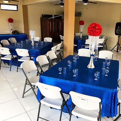 Sala con sillas, mesas, manteles azules y centros de mesa de fiesta